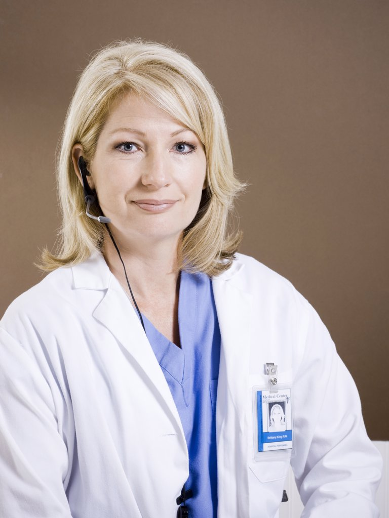 Stock Photo: 1660R-60396 Studio portrait of female doctor using headset