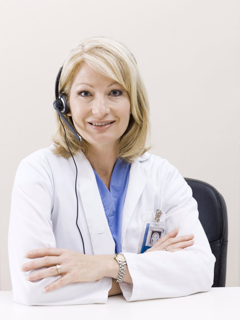 Mature woman talking on headset, studio shot : Stock Photo