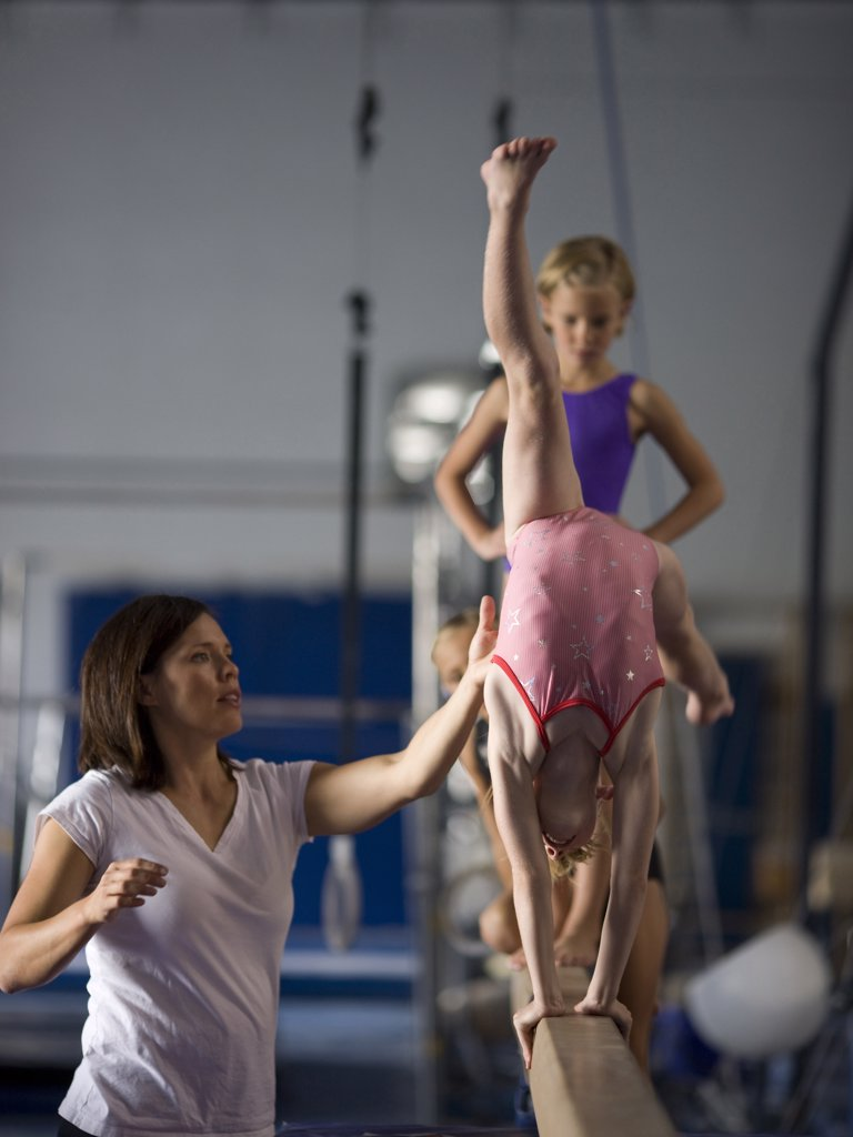 Stock Photo: 1660R-60571 USA, Utah, Orem, Instructor helping gymnasts (6-9) to perform handstand on beam