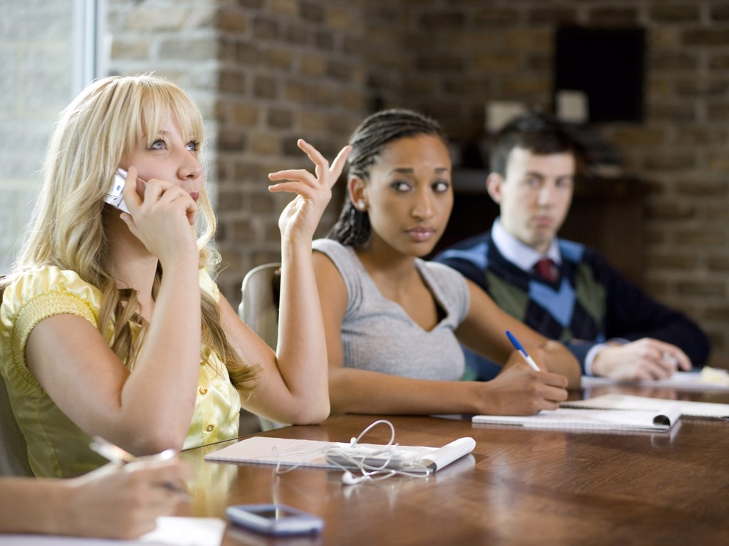 woman on her cell phone during a meeting : Stock Photo