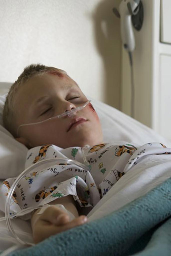 Stock Photo: 1660R-6141 Boy lying in a hospital bed breathing through a tube