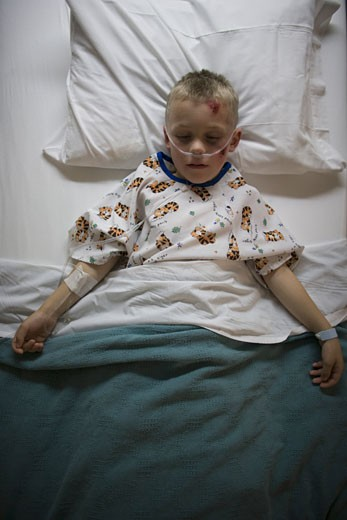 Stock Photo: 1660R-6143 High angle view of a boy lying in a hospital bed breathing through a tube