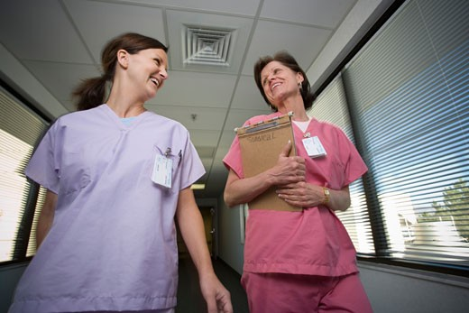 Close-up of two female nurses walking in a corridor : Stock Photo