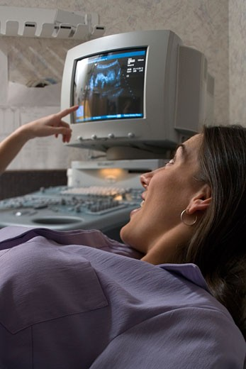 Stock Photo: 1660R-6197 Pregnant woman lying on a hospital bed looking at her ultrasound result