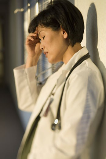 Stock Photo: 1660R-6236 Profile of a female doctor with her hand on her forehead