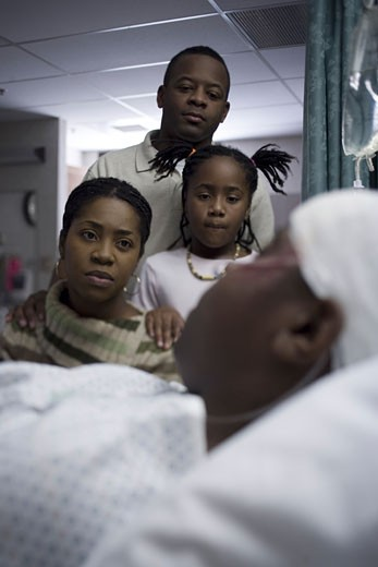 Stock Photo: 1660R-6273 Parents and their daughter looking at a teenage boy in the hospital