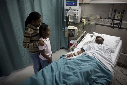 Stock Photo: 1660R-6277 High angle view of a mother and daughter in a hospital looking at a teenage boy