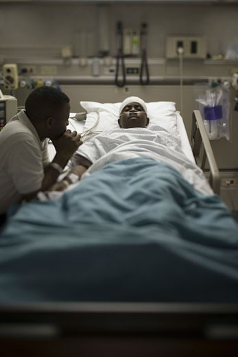 Stock Photo: 1660R-6286 Profile of a father sitting beside his son lying on a hospital bed