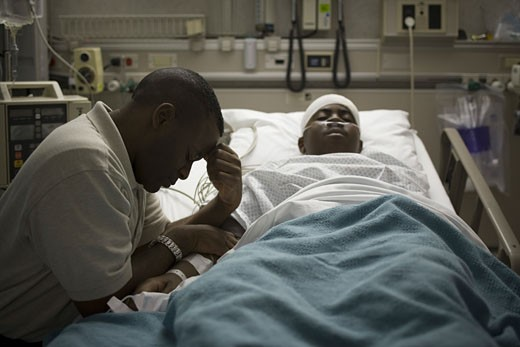 Stock Photo: 1660R-6287 Profile of a father sitting beside his son lying on a hospital bed