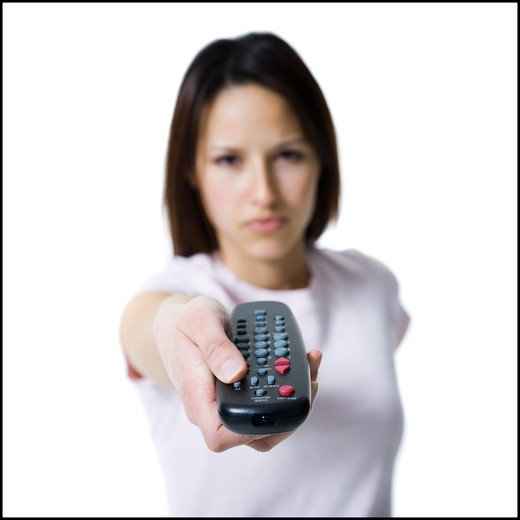 Stock Photo: 1660R-63047 Woman pointing and pressing a handheld remote control