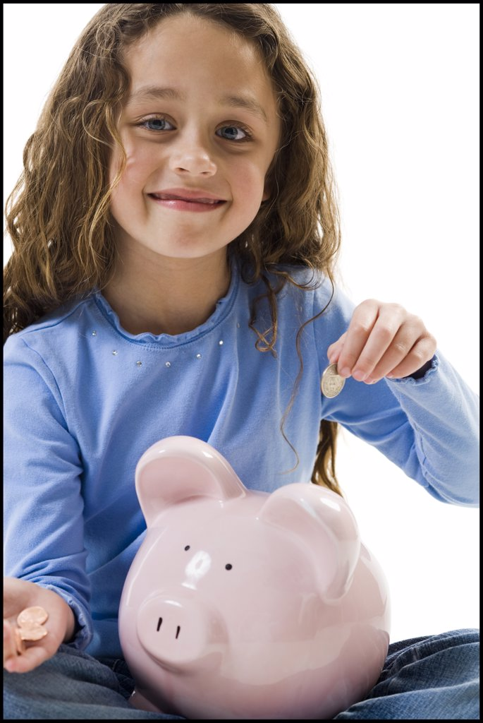 Stock Photo: 1660R-63128 Young girl depositing money in piggy bank