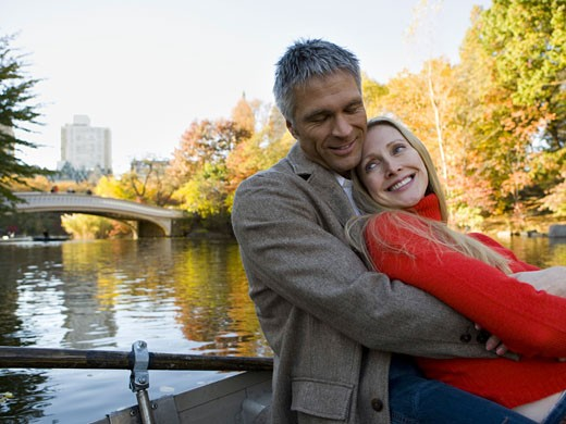 Stock Photo: 1660R-6333 Couple embracing while sitting on a boat