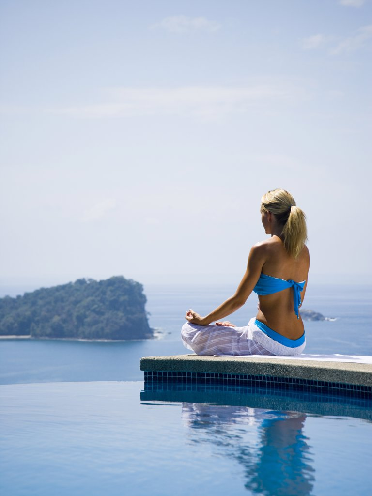 Woman performng yoga exercises by infinity pool : Stock Photo