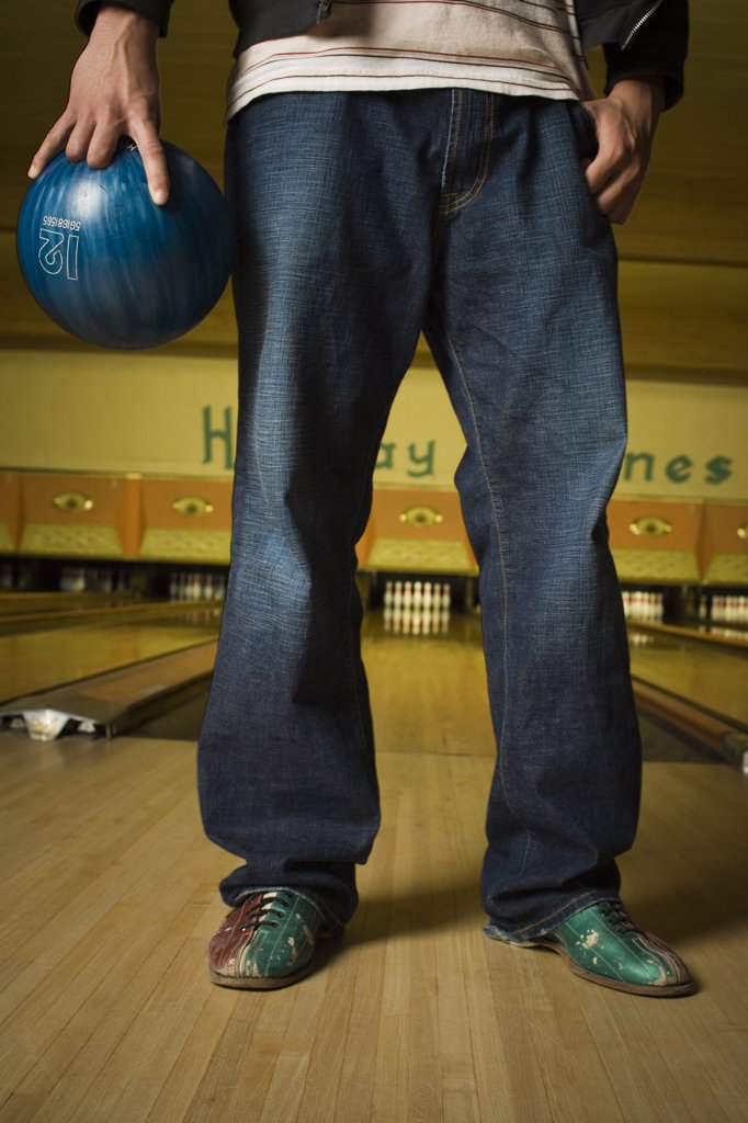 Low section view of a young man holding a bowling ball : Stock Photo