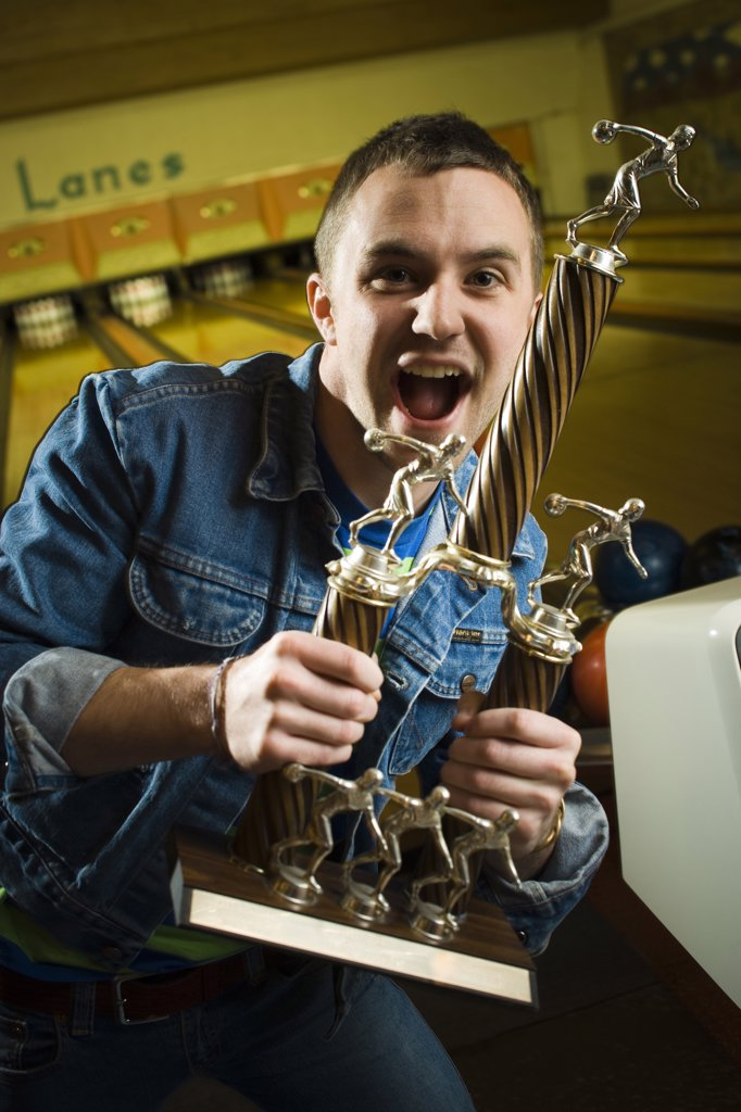 Stock Photo: 1660R-63493 Portrait of a young man holding a bowling trophy and dancing