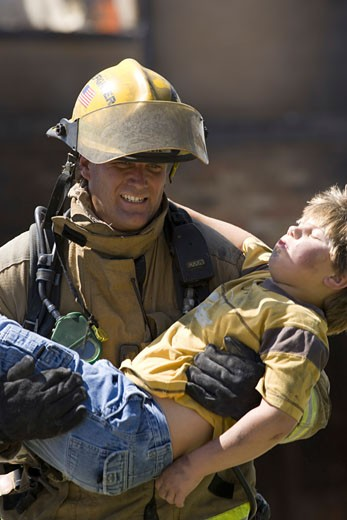 Firefighter carrying a wounded boy : Stock Photo