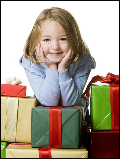 Portrait of a girl leaning over a stack of gifts : Stock Photo