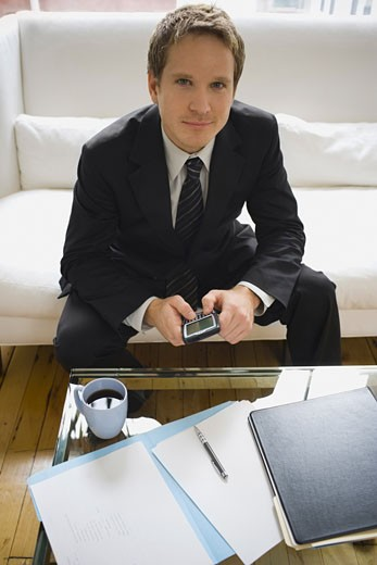 Portrait of a businessman holding an electronic organizer : Stock Photo
