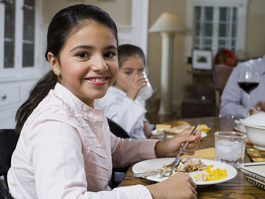 Portrait of a teenage girl sitting at a dining table and smiling : Stock Photo