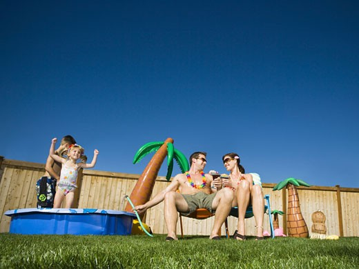 Low angle view of parents with their children playing in a wading pool : Stock Photo