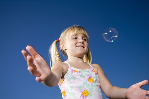 Stock Photo: 1660R-7350 Low angle view of a girl catching a bubble