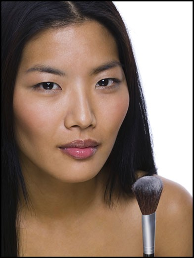 Portrait of a woman with a make-up brush : Stock Photo