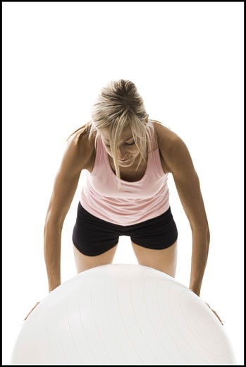 Close-up of a young woman exercising on a fitness ball : Stock Photo