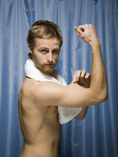Stock Photo: 1660R-7730 Profile of a young man flexing his biceps