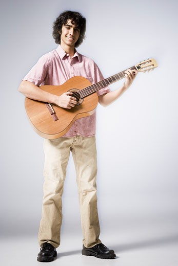 Stock Photo: 1660R-7767 Portrait of a teenage boy playing the guitar