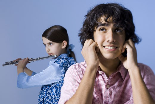 Close-up of a teenage girl playing the flute behind a teenage boy : Stock Photo