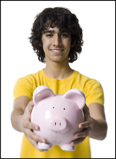 Portrait of a teenage boy holding a piggy bank : Stock Photo