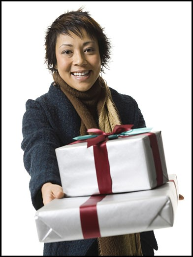 Portrait of a young woman holding gifts : Stock Photo