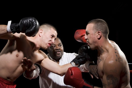 Referee separating two boxers during a fight : Stock Photo