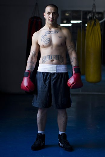 Portrait of a young man wearing boxing gloves : Stock Photo