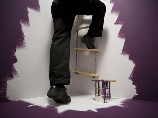 Stock Photo: 1660R-7862 Low section view of a mid adult man climbing a ladder