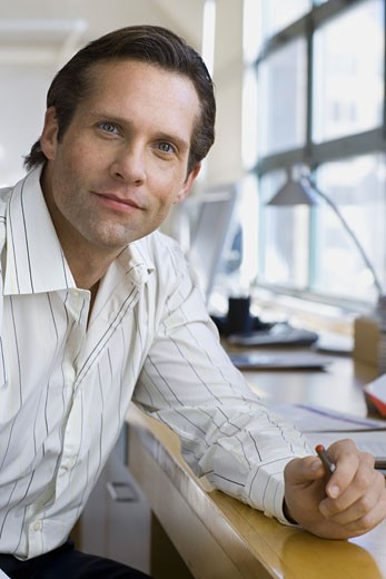 Portrait of a businessman resting his hand on the table : Stock Photo