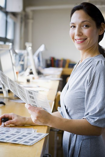 Portrait of a woman looking through slide sheets : Stock Photo