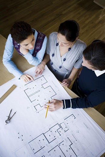 Stock Photo: 1660R-7938 High angle view of three architects looking at blueprints