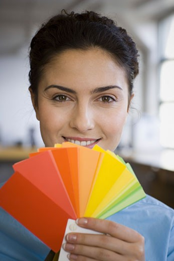 Portrait of a young woman holding color swatches : Stock Photo