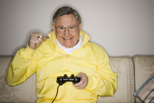 Close-up of a senior man playing a video game : Stock Photo