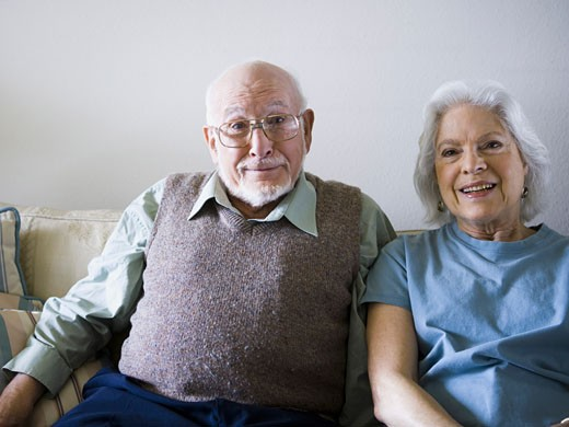 Stock Photo: 1660R-8124 Portrait of a senior couple sitting on a couch and smiling