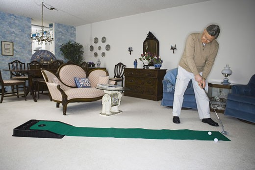 Stock Photo: 1660R-8153 Senior man playing golf in the living room