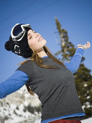 Close-up of a young woman standing with her arms outstretched : Stock Photo