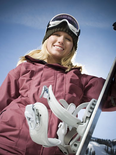 Low angle view of a young woman holding a snowboard : Stock Photo