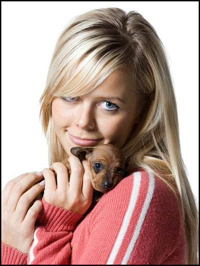 Stock Photo: 1660R-8491 Portrait of a young woman hugging a puppy