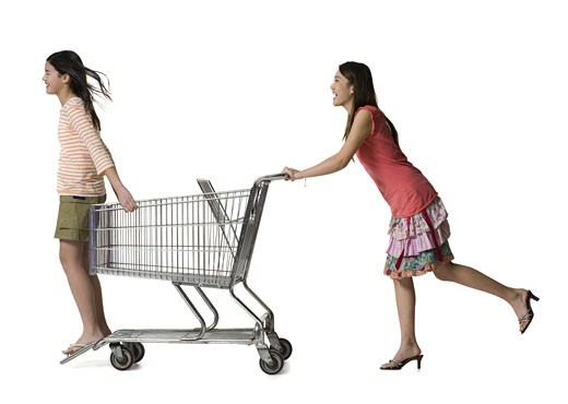 Profile of a young woman pushing a teenage girl in a shopping cart : Stock Photo