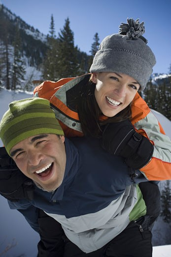 Portrait of a woman ridding piggyback on a man : Stock Photo