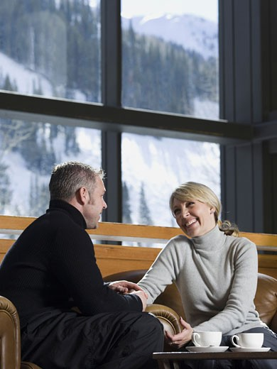 Man and woman chatting in a ski lodge : Stock Photo