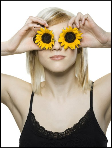 Stock Photo: 1660R-8710 Close-up of a young woman holding sunflowers in front of her eyes