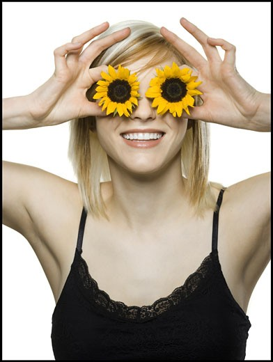 Stock Photo: 1660R-8712 Close-up of a young woman holding sunflowers in front of her eyes